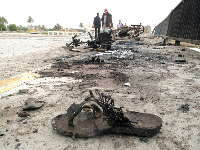 A bloodied slippers and a destroyed motor bike are seen following a suicide bombing along the center of the al-Hauz Bridge which lies across the Euphrates River linking the southern district with the central and northern district of the city of Ramadi, west of the capital Baghdad on March 30, 2014 (AFP Photo)