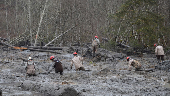Washington National Guard rescue workers make their way through the mud and wreckage left behind by Saturday's mudslide as they look for signs of missing persons, in Oso, Washington March 27, 2014.(Reuters / Matthew Sissel)