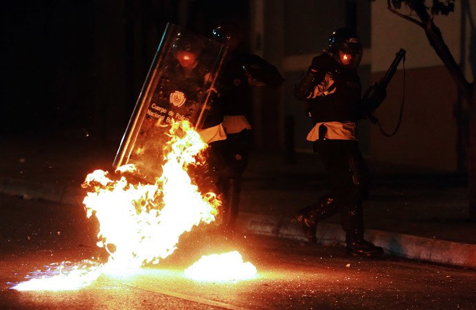 Riot policemen protect themselves from molotov cocktails thrown by anti-government activists during a protest, in Caracas on March 31, 2014. (AFP Photo / Juan Barreto)