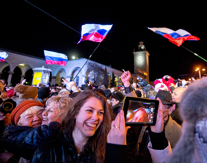 People celebrate the transition to Moscow time near a city clock tower at a railway station in Simferopol on March 30, 2014. (AFP Photo / Dmitry Serebryakov)