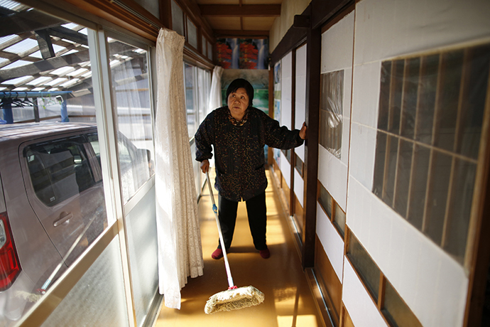 Kimiko Koyama, 69, who evacuated from the Miyakoji area of Tamura three years ago, dusts off her house after she returned to her home with her husband Toshio, 76, in Tamura, Fukushima prefecture April 1, 2014. (Reuters / Issei Kato)