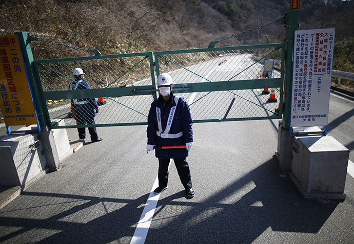 Security personnel stand guard near a steel gate that marks the border between Tamura and Okuma town in Okuma town, Fukushima prefecture April 1, 2014. (Reuters / Issei Kato)