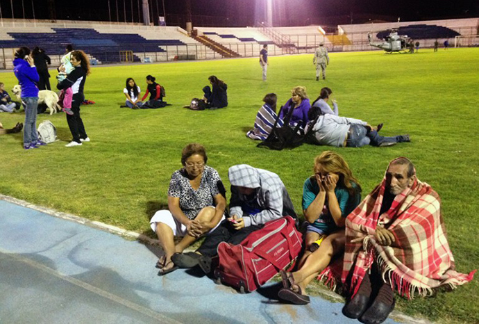 Locals take refuge at the city stadium following a tsunami alert after a powerful 8.0-magnitude earthquake hit off Chile's Pacific coast, on April 1, 2014 in Iquique. (AFP Photo / Aldo Solimano)