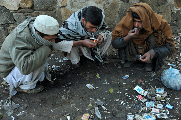 Afghan drug addicts smoke heroin on a street in Jalalabad on February 7, 2014. (AFP Photo / Noorullah Shirzada)