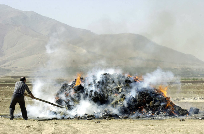 An Afghan official sets fire to seized drugs, including more than 2,5 tons of opium, more than 4 tons of hasish, and some 169 kilos of heroin, outside Kabul, 23 September 2004. (AFP Photo / Shah Marai)