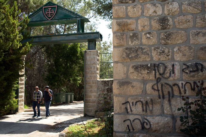 "People leave the Deir Rafat Catholic convent whose walls were sprayed with a graffiti (R) reading in Hebrew ""Jesus monkey, Maria cow, Tag price"" on April 1, 2014 near the Israeli city of Beit Shemesh, west of Jerusalem. (AFP Photo / Menahev Kahana)"