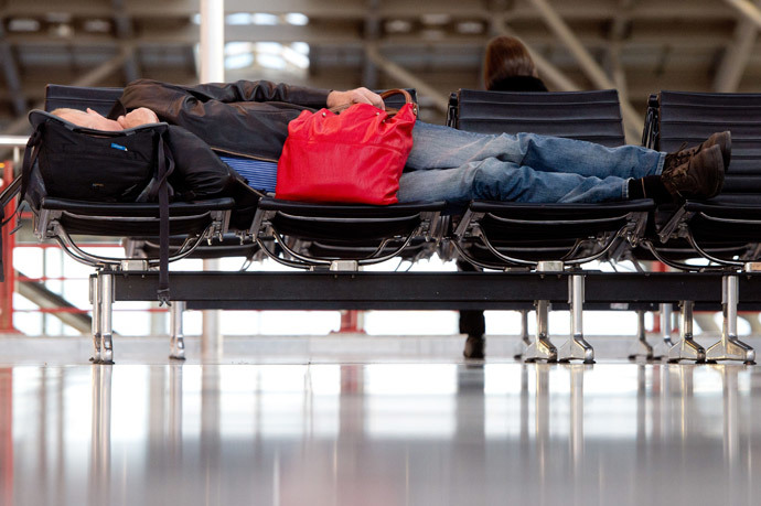 A man sleeps at the airport in Stuttgart, southern Germany, on April 2, 2014. (AFP Photo / DPA / Sebastian Kahnert / Germany out)