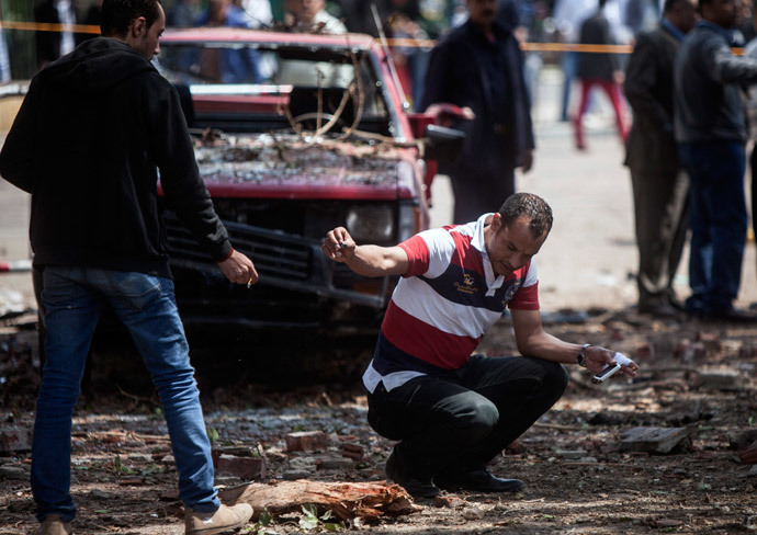 A member of the Egyptian security personnel inspects the scene after twin bombs struck police posts near Cairo University in the centre of Egypt's capital on April 2, 2014. (AFP Photo / Mahmoud Khaled)