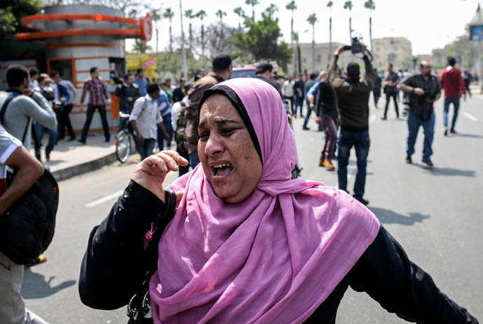 An Egyptian woman runs for cover as a bomb struck a police post near Cairo University in the centre of Egypt's capital on April 2, 2014. (AFP Photo / Mohamed El-Shahed)