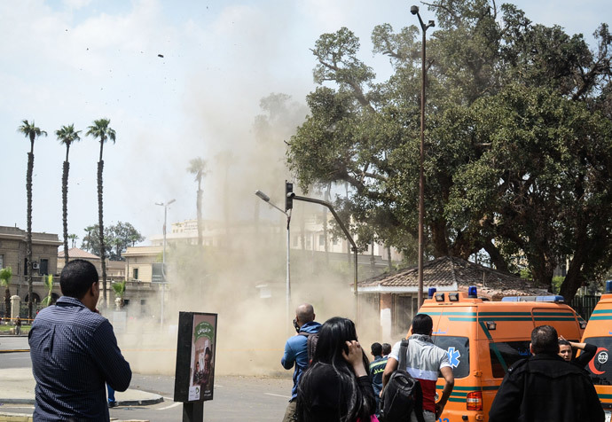 Egyptians look on as a bomb struck a police post near Cairo University in the centre of Egypt's capital on April 2, 2014, which was followed by two further blasts. (AFP Photo / Mohamed El-Shahed)