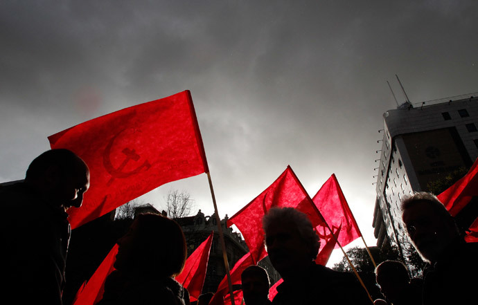 Demonstrators hold flags of the Communist Party during an anti-NATO march in downtown Lisbon (Reuters / Juan Medina)