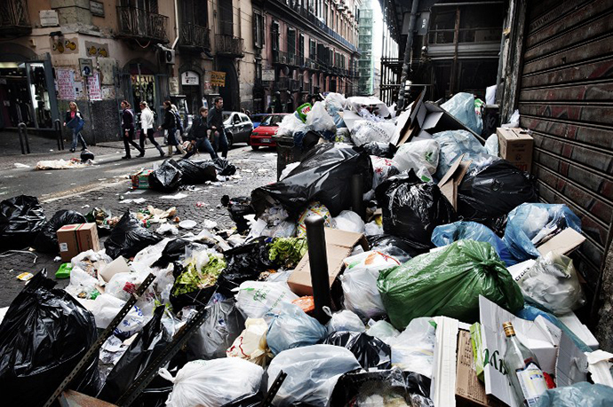 Pedestrians walk by uncollected garbage downtown Naples on October 20, 2010 hours after local residents skirmished with riot police and set a bus alight near Naples. (AFP Photo / Roberto Salomone)