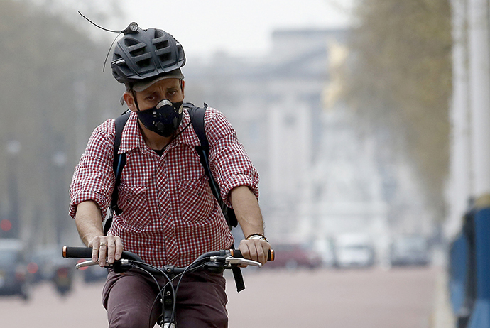 A cyclist wears a mask as he cycles near Buckingham Palace in London April 2, 2014. (Reuters / Luke MacGregor)