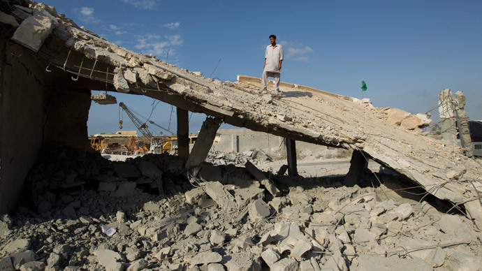 A man stands on the remnants of a school and mosque bombed by NATO forces according to Libyan officials in a village on the outskirts of Zlitan, 160km (99 miles) east of Tripoli, July 25, 2011.(Reuters / Caren Firouz)