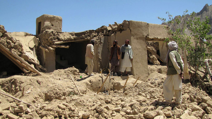 Afghan villagers stand at a house which was hit by a NATO airstrike in Sajawand village in Logar province, south of Kabul on June 6, 2012.(AFP Photo / Sabawoon Amarkhil )