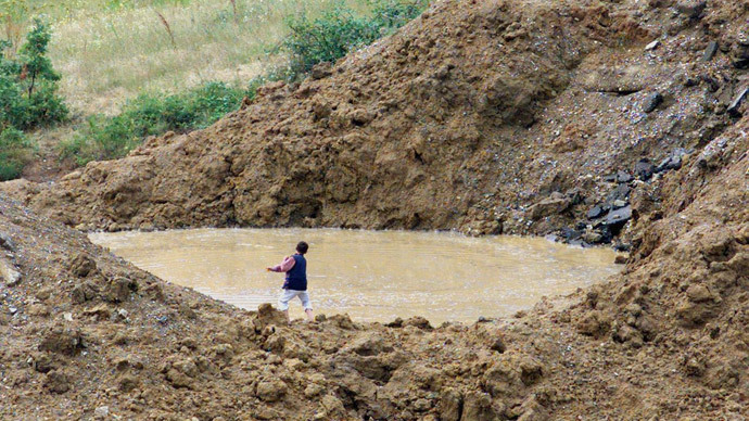 A Kosovar boy throws stones in a the flooded crater of bomb dropped during NATO strikes against Yugoslavia 01 July 1999 on a road between Malisevo and Pristina, southwestern Kosovo.(AFP Photo / Jean-Philippe Ksiazek)