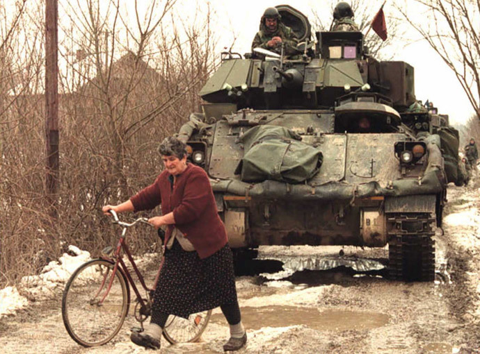 A Bosnian Serb woman makes her way between vehicles of a US troop convoy of the NATO peace enforcement forcce (IFOR) on a dirt road near Pelagicevo in a Serb-held area of the northern Bosnian Posavina corridor 02 January 1996.(AFP Photo / Pascal Guyot)