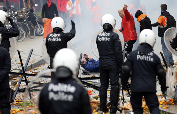 An injured demonstrator lies on the ground after being hit by a stone thrown by other demonstrators during a European trade unions protest against austerity measures, in central Brussels April 4, 2014. (Reuters/Francois Lenoir)
