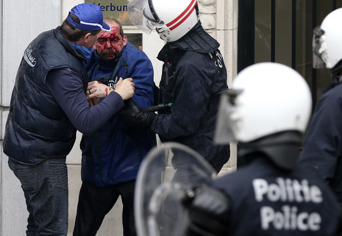 An injured demonstrator is helped by riot police officers after being hit by a stone thrown by other demonstrators during a European trade unions protest against austerity measures, in central Brussels April 4, 2014. (Reuters/Francois Lenoir)
