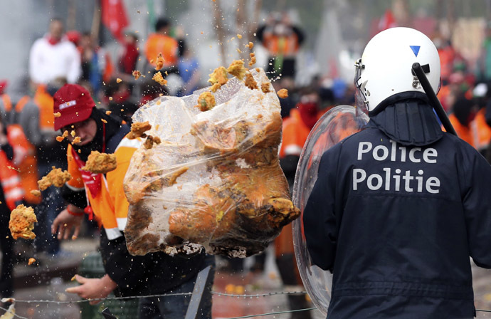 A demonstrator throws garbage towards riot police officers during a European trade unions protest against austerity measures, in central Brussels April 4, 2014. (Reuters/Francois Lenoir)