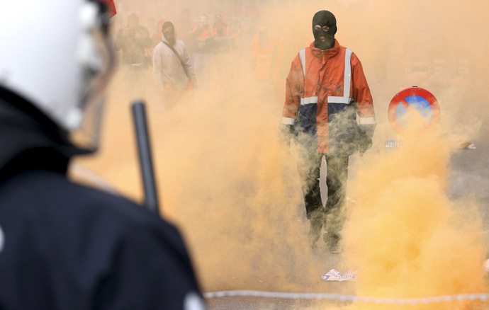 A demonstrator stands in front of riot police officers during a European trade union protest against austerity measures, in central Brussels April 4, 2014. (Reuters/Francois Lenoir)