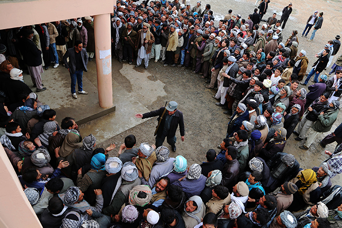 An Afghan policeman tries to keep order as voters wait in line outside a polling station inBamiyan on April 5, 2014. (AFP Photo / Shefayee)