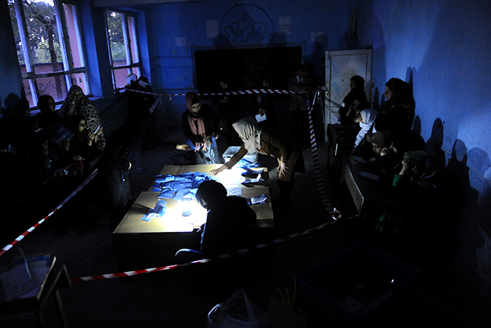 Afghan election workers sort presidential ballots by the light of a lantern after a polling station was closed for voting in the northwestern city of Herat on April 5, 2014. (AFP Photo / Aref Karimi)