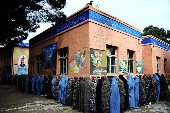 Afghan women queue outside a school to vote in presidential elections in the northwestern city of Herat on April 5, 2014. (AFP Photo / Aref Karimi)