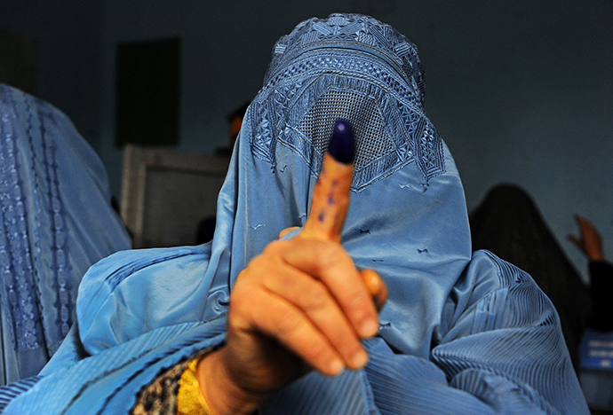 An Afghan woman shows her inked finger after voting at a polling station in the northwestern city of Herat on April 5, 2014. (AFP Photo / Aref Karimi)