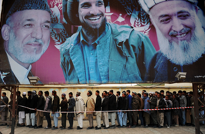 Afghan residents wishing to vote line up underneath a billboard showing images of Afghan President Hamid Karzai (L) and of deceased Afghan figures Burhandin Rabani (R) and Ahmad Shah Massoud (C) outside a polling station in Mazar-i-Sharif on April 5, 2014. (AFP Photo / Farshad Usyan)