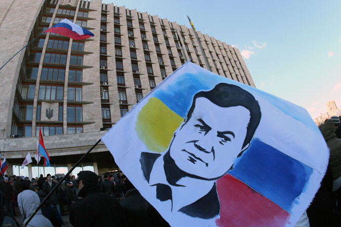 A demonstrator holds a flag with the portrait of deposed Ukrainian President Viktor Yanukovych during a rally of pro-Russia supporters outside the regional government administration building in the center of the eastern Ukrainian city of Donetsk during on April 5, 2014. (AFP Photo)