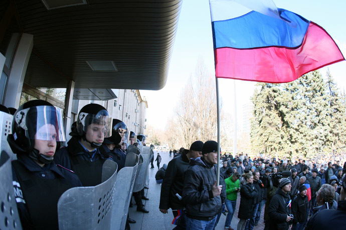 A man holds a Russian flag as police officers stand guard outside the regional government administration building in the center of the eastern Ukrainian city of Donetsk during a rally of pro-Russia supporters on April 5, 2014. (AFP Photo)