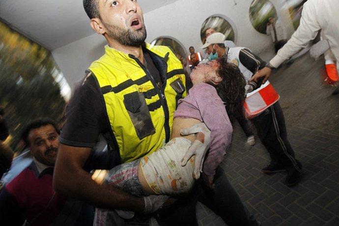 A Palestinian rescue worker carries the body of a child from the al-Dallu family into the hospital in Gaza City on November 18, 2012, after seven members of the al-Dallu family, including four children, were among nine people killed when an Israeli missile struck a family home in Gaza City, the health ministry said. (AFP Photo / Mohammed Abed)