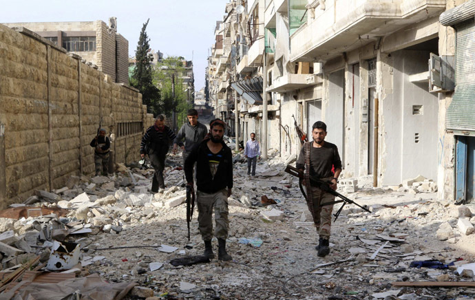 Free Syrian Army fighters walk with their weapons along a damaged street in Bustan al-Basha district in Aleppo April 6, 2014. (Reuters/Mahmoud Hebbo)