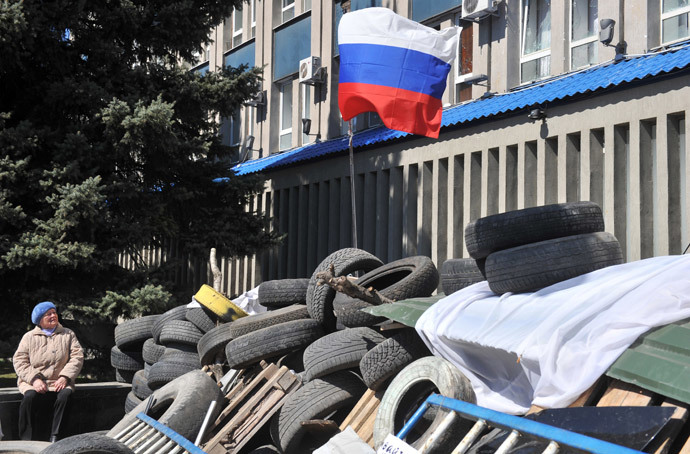 An elderly woman looks at the Russian flag set up by pro-Russian activists at a barricade blocking access to the Ukrainian Security Service building in the eastern Ukrainian city of Lugansk on April 8, 2014.(AFP Photo / Genya Savilov)