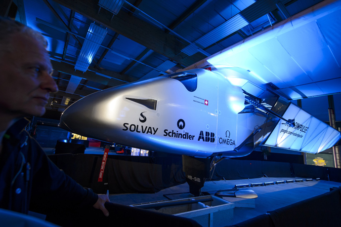 A staff of Solar Impulse stands next to the second solar-powered plane, the HB-SIB, which Swiss pilots Bertrand Piccard and Andre Borschberg aim to take on a round-the-world voyage next year, during is unveiling on April 9, 2014 in Payerne (AFP Photo / Fabrice Coffrini)