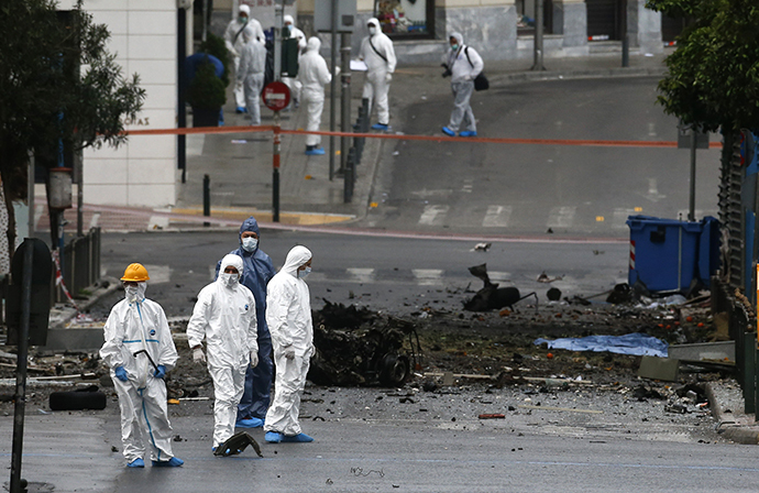 Forensic experts search for evidence on a street where a car bomb went off in Athens April 10, 2014. (Reuter / Alkis Konstantinidis)