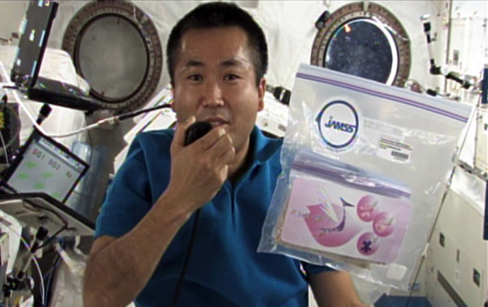Japanese astronaut Koichi Wakata holding a pack of cherry sheeds in the International Space Station on April 13, 2009 (AFP Photo / JAXA)