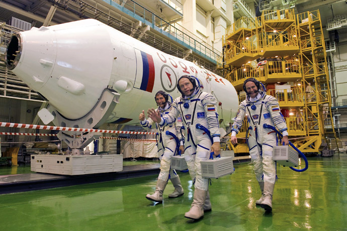 U.S. astronaut Michael Hopkins (L), Russian cosmonauts Oleg Kotov (C) and Sergey Ryazanskiy walk to attend a training session at the Baikonur cosmodrome, September 14, 2013. (Reuters/Sergei Remezov)