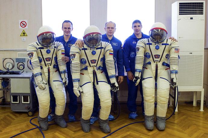 U.S. astronaut Michael Hopkins (R), Russian cosmonauts Oleg Kotov (C) and Sergey Ryazanskiy pose for a picture at the Baikonur cosmodrome, September 14, 2013. (Reuters/Sergei Remezov)