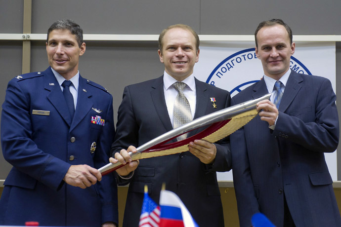 U.S. astronaut Michael Hopkins (L), Russian cosmonauts Oleg Kotov (C) and Sergey Ryazanskiy hold an Olympic torch at the Star City space centre outside Moscow, September 6, 2013. (Reuters/Sergei Remezov)