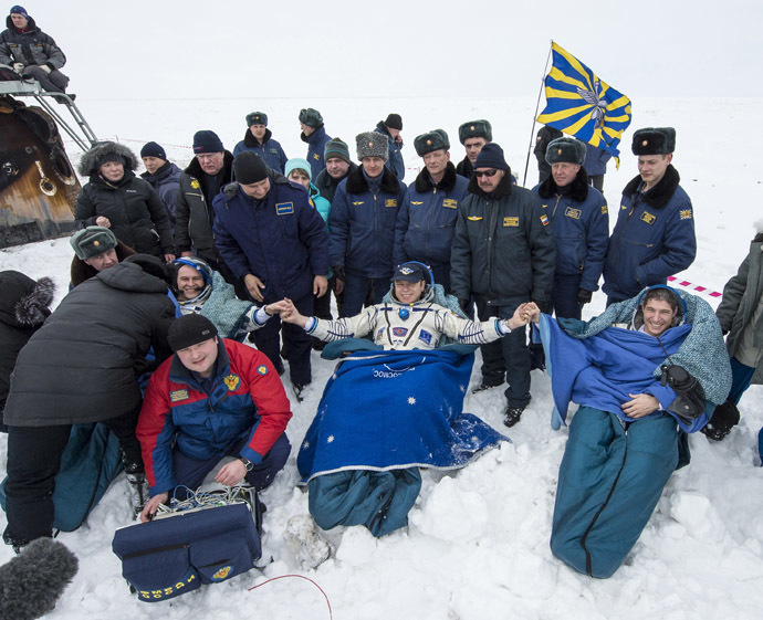 Former ISS commander Oleg Kotov (C) and flight engineers Sergei Ryazansky (L) and Michael Hopkins from NASA sit in chairs outside the Soyuz TMA-10M capsule shortly after they landed in a remote area southeast of the town of Zhezkazgan in central Kazakhstan, March 11, 2014. (Reuters/Bill Ingalls/NASA)