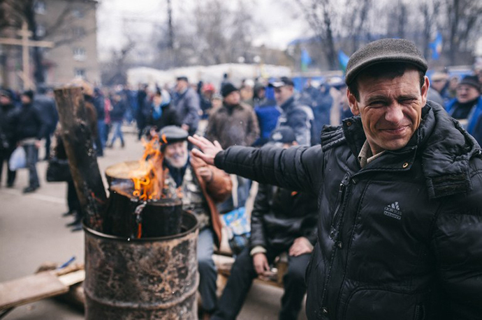A pro-Russian activist squints as he warms himself near a fire outside the headquarters of Ukraine's security agency building in the eastern Ukrainian city of Lugansk on April 12, 2014. (AFP Photo / Dimitar Dilkoff)