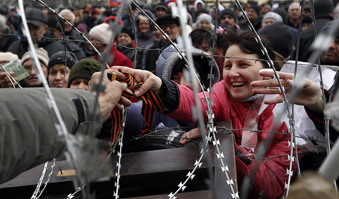A pro-Russian activist reaches through razor wire to receive a ribbon of St. George, a well-known Russian symbol of military valor which has become a symbol of pro-Russian protesters, at a barricade outside the regional state administration building in Donetsk, eastern Ukraine, on April 12, 2014. (AFP Photo / Max Vetrov)