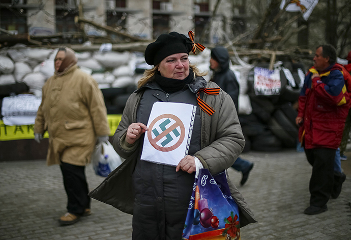 A pro-Russia protester holds an anti-swastika sign in front of a barricade outside a regional government building in Donetsk, in eastern Ukraine April 11, 2014. (Reuters / Gleb Garanich)