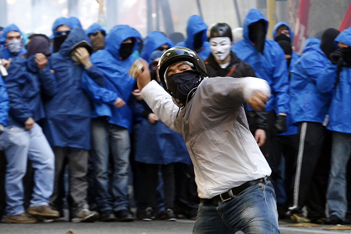 A demonstrator throws a stone at policemen during a protest in downtown Rome April 12, 2014. (Reuters / Alessandro Bianchi)