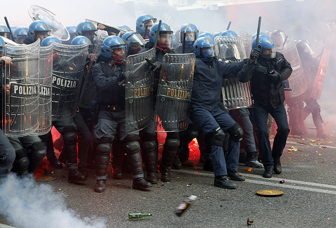 Policemen take shelter from bottles and flares thrown by demonstrators during a protest in downtown Rome April 12, 2014. (Reuters / Alessandro Bianchi)
