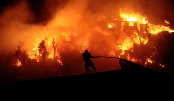 A firefighter works near houses on fire in Valparaiso, 110 km west of Santiago, Chile, on April 12, 2014. (AFP Photo/Felipe Gamboa)