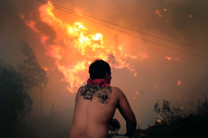 A local stares at houses in flames during a fire in Valparaiso, 110 km west of Santiago, Chile, on April 12, 2014. (AFP Photo/Felipe Gamboa)