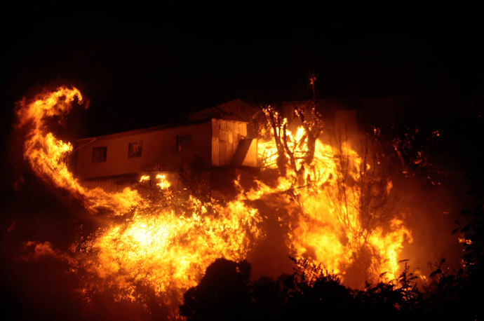 View of burning houses during a fire in Valparaiso, 110 km west of Santiago, Chile, on April 12, 2014. (AFP Photo/Felipe Gamboa)